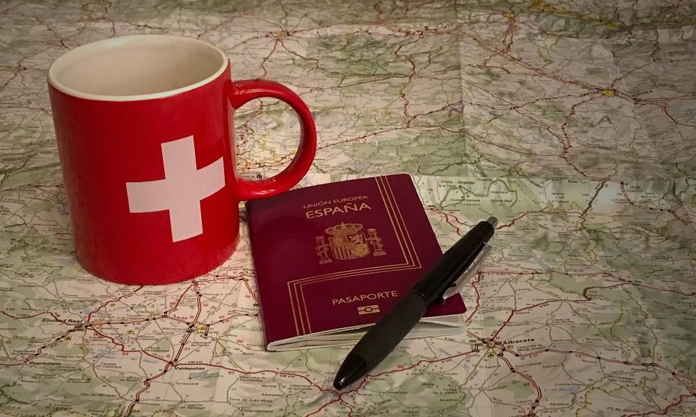 Taza de Suiza y pasaporte de España
