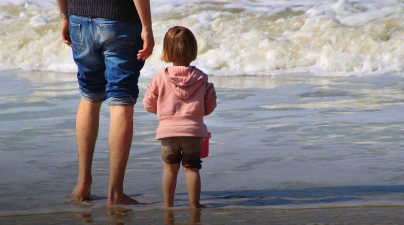 Niña en la playa con su padre