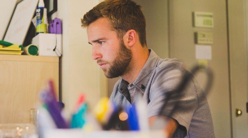 Trabajador en oficina con bolígrafos